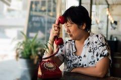 Düsterer Telefonanruf der Asiatinnen in einer Kaffeestube Stockfotos