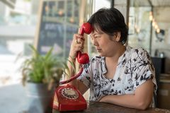 Düsterer Telefonanruf der Asiatinnen in einer Kaffeestube Stockfoto