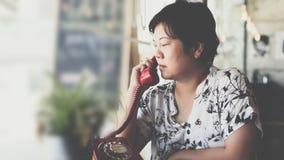 Düsterer Telefonanruf der Asiatinnen in einer Kaffeestube Lizenzfreies Stockfoto
