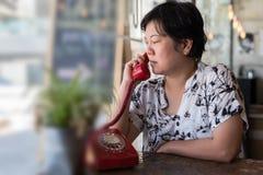 Düsterer Telefonanruf der Asiatinnen in einer Kaffeestube Lizenzfreies Stockbild