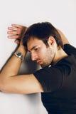 Düsterer und trauriger Kerl in einem schwarzen T-Shirt und in einer Uhr auf einer Hand Stockfotografie