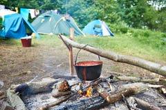 Dęciak z polewką na ogniska i turysty namiotach Zdjęcia Royalty Free