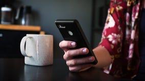 Dłoń kobiety używa smartfona przy stole. zdjęcie wideo