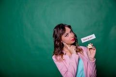 Długa kędzierzawego włosy dziewczyna stawia czoło wybór na zieleni, trzyma małego dom przy jej rękami z wiadomością pytanie fotografia royalty free