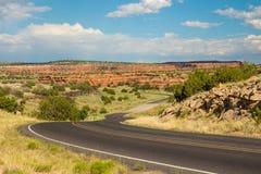 Długa osamotniona droga po środku pustyni pod niebieskim niebem zdjęcia stock