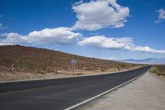 Długa prosta droga przez jałowego pustynia krajobrazu Kalifornia Zdjęcia Royalty Free