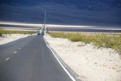 Długa prosta droga przez jałowego pustynia krajobrazu Kalifornia Obrazy Stock