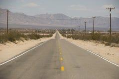 Długa prosta droga przez jałowego pustynia krajobrazu Kalifornia Zdjęcie Royalty Free