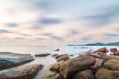 Długa ujawnienie skały plaża przy małą wyspą Obrazy Stock
