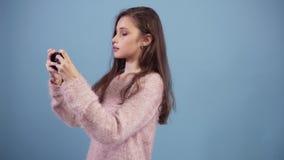 Długa z włosami caucasian nastoletnia dziewczyna uśmiecha się gra wideo na jej smartphone na błękicie i entuzjastycznie bawić się zbiory
