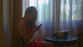 Długa Z włosami dziewczyna Używa Smartphone przeciw okno w pokoju zbiory