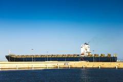 Długi ładunku statek dokujący na nadbrzeżu w doku porcie Zdjęcia Stock
