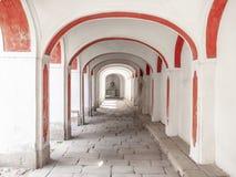 Długi arkady corridior z fasadą i brukującą podłoga białą i czerwoną Obraz Royalty Free