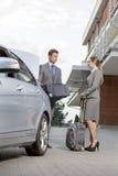 Długi biznesowa para z bagażem na zewnątrz hotelu Fotografia Stock