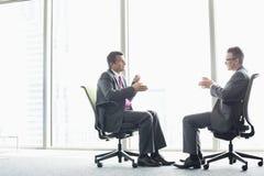 Długi boczny widok biznesmeni dyskutuje podczas gdy siedzący na biurowych krzesłach okno Zdjęcie Royalty Free