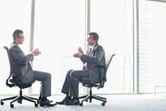 Długi boczny widok biznesmeni dyskutuje podczas gdy siedzący na biurowych krzesłach okno Zdjęcia Royalty Free