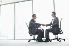 Długi boczny widok biznesmeni trząść ręki podczas gdy siedzący na biurowych krzesłach okno Obraz Royalty Free