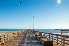 Długi Drewniany molo, Błękitny morze i niebieskie niebo, fotografia stock