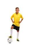 Długi futbolista chłopiec stawia jego ręki w stronach i stawia jego nogę na piłce odizolowywającej na białym tle obraz royalty free