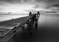 Długi most nad morzem z pięknym wschodem słońca w czerni a Zdjęcia Stock