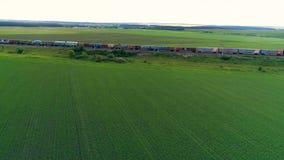 Długi pociąg towarowy rusza się wśród zielonych poly zbiory
