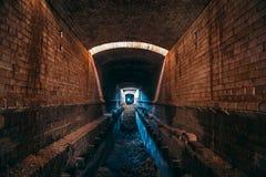 Długi podziemny ceglany tunel lub atmosfera przemysłowa korytarza, przerażającej i horroru, perspektywa zdjęcia stock