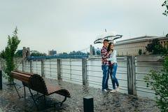 Długi portret potomstwa dosyć kocha pary przytulenie pod parasolem podczas gdy cieszący się krajobraz Ostrow zdjęcia stock