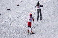 Długi portret szczęśliwa narciarki pozycja z nartami na skłonie ono uśmiecha się przy kamerą w błękitnym narciarskim kostiumu, ma fotografia royalty free