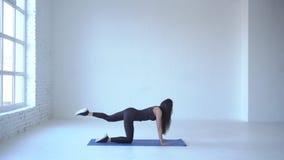 Długi widok chuderlawy sportowy trener wykonuje ćwiczenie osła kopnięcie na joga macie w białym studiu 4K zbiory wideo