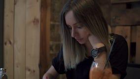 Długi z włosami blondynki kobiety obsiadanie w kawiarni robi niektóre notatkom w jej notatniku nowożytnym zamyśleniu i Szkło zbiory