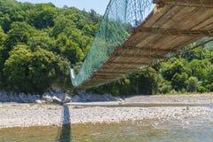 Długi zwyczajny zawieszenie most przez halnego rzecznego Bzyb zdjęcie stock