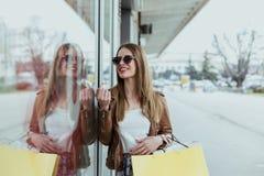 Długie włosy dziewczyna patrzeje na sprzedaży w sklepowym okno zdjęcie royalty free
