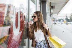 Długie włosy dziewczyna patrzeje na sprzedaży w sklepowym okno obraz royalty free