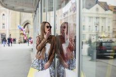 Długie włosy dziewczyna patrzeje na sprzedaży w sklepowym okno zdjęcie stock