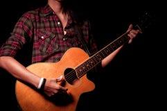 Długie włosy facet bawić się gitarę akustyczną Fotografia Royalty Free