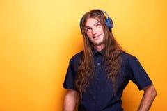 Długie włosy faceta słuchająca muzyka robi śmiesznym twarzom zdjęcie royalty free