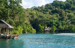 Długiego ogonu łódź parkująca niedaleka wzdłuż plaży chałupa Zdjęcia Stock