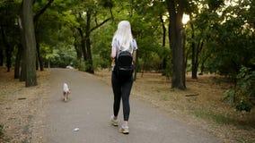 Długiej blondynki z włosami młoda kobieta w czarnych leggings i plecaka odprowadzenie greem parkiem z jej zwierzęciem domowym lea zdjęcie wideo