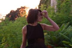 Długość portret dama z czarnym sukni i skrótu falistym ciemnym włosy, patrzeje w samochodzie z słońcem za ona w su fotografia royalty free
