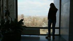 Długowłosa brunetki kobieta stoi blisko dużego mówienia na telefonie i okno zbiory wideo