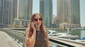 Długowłosa dziewczyna chodzi przez miasta Dubaj i opowiada na telefonie zbiory wideo