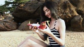 Długowłosa dziewczyna na plaży demonstruje ciała smok owoc egzot zbiory