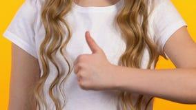 D?ugow?osa dziewczyna pokazuje aprobaty, dzieci poleca, sukces, w g?r? zbiory