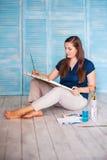 Długowłosy żeński artysta maluje coś na kanwie Zdjęcie Royalty Free