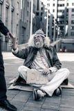 Długowłosy brudzi mężczyzny obsiadanie na zimnie mlejącym z kartonowym nameplate obrazy royalty free