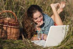 Długowłosy dziewczyny lying on the beach przy laptopem i ono uśmiecha się Obraz Royalty Free