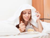 Długowłosy kobiety łasowania cukierki tort pod bielu prześcieradłem w łóżku Obraz Stock