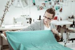 Długowłosy potomstwa fasonują krawcowej z tatuażem pracuje z tkaniną obraz stock