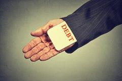 Długu pożyczania pojęcie biznesowy mężczyzna chuje dług kartę w kostiumu rękawie Obraz Stock