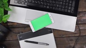 Dźwigowy dźwignięcie, odgórnego widoku telefon z zielonym ekranem jest na laptopie desktop projektant, fotograf zbiory